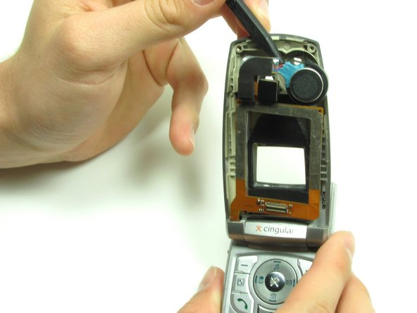 Carefully slide the spudger behind the main ribbon in order to separate it from the inside cover of the phone.