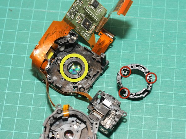 Three screws (red circles, shown here already removed) hold the ring surrounding the rear lens element.