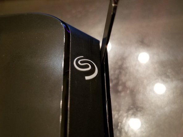 With the help of the pick, get the spudger into the crack next to the seagate logo (picture 1).