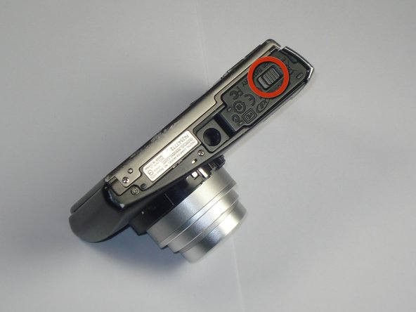 Using your thumb, slide the gray button to open the battery compartment.