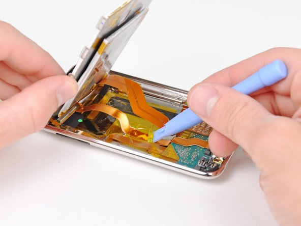 Use the edge of an iPod opening tool to remove the piece of tape covering the display data cable.