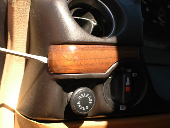 Let's begin with the strips of wood trim that run across the dash. These pieces are glued in place to a metal backing plate. After all these years the glue is often quite weak and so the wood trim can be gently pried off with a screw diver, or sometimes simply by hand.