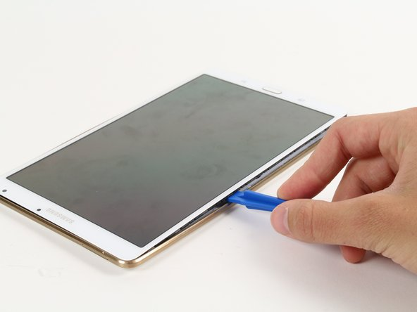 By sliding the plastic opening tool around the rim of the device, carefully continue to pry apart the screen and back cover.