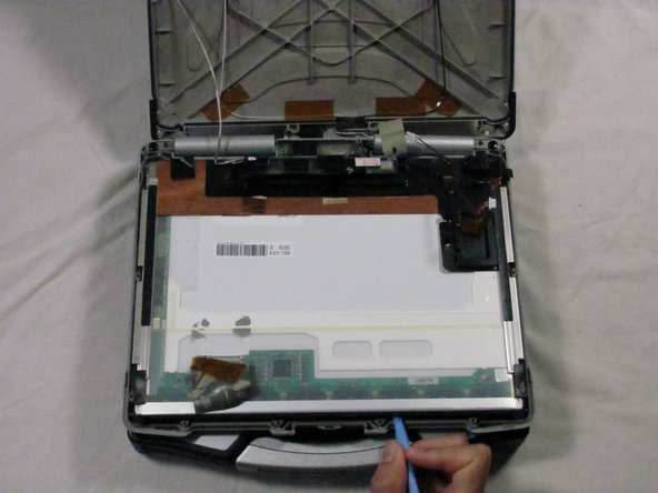 Using a plastic opening tool, lift the screen as shown from the case and pull free.