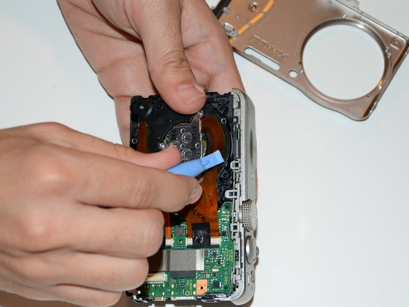 Release the top cover by lifting several tabs with the plastic opening tool. Go gently to avoid breaking them.