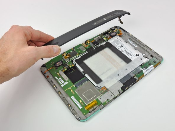 After disconnecting the volume button ribbon cable and removing two screws, the top portion of the upper case lifts off.