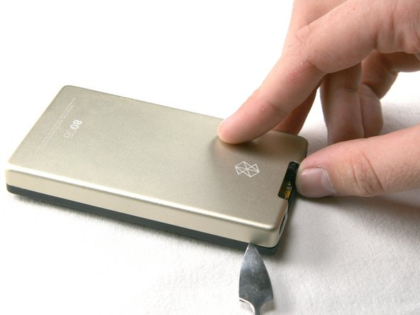 Using a metal spudger or Zune opening tool, remove the aluminum backing starting from the top. There are 5 clips on each side and two on the bottom.