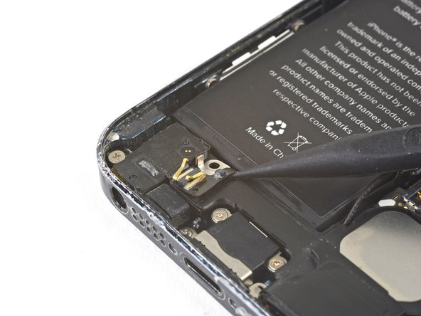 Slide the point of a spudger underneath the spring contact flex cable below the battery and gently loosen it from the speaker enclosure.
