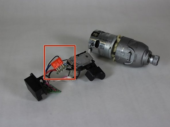 Identify the translucent orange fuse cartridge connected by a thick red wire and a thick white wire.