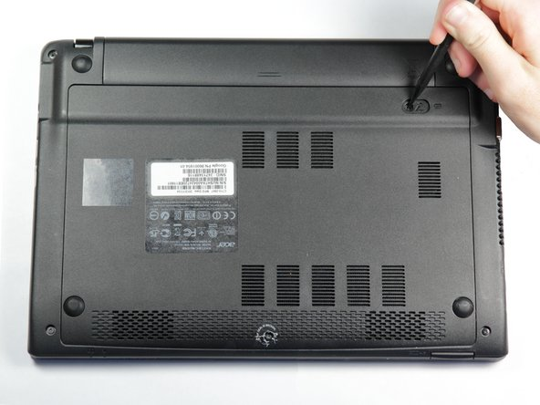Place the laptop on a flat surface with the bottom side facing up.
