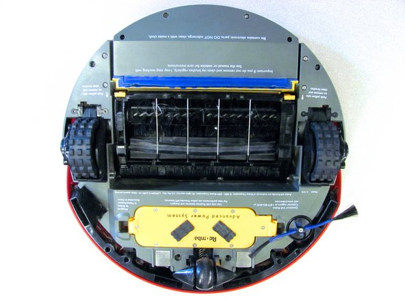 Lay the Roomba upside down on a flat surface with the blue strip away from you.