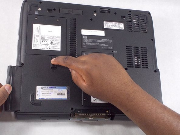 While still holding the  switch up, remove the battery.