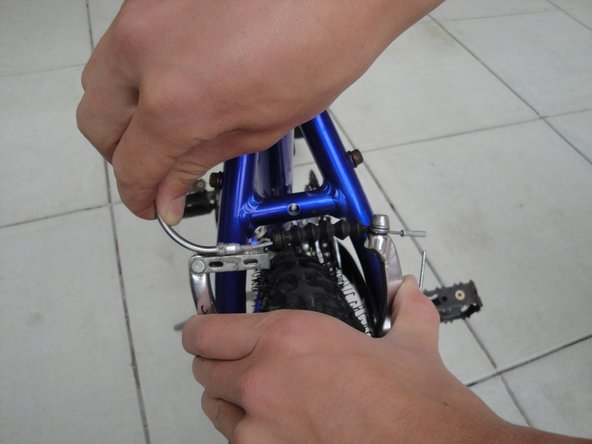 Squeeze the brake arms together and lift the brake cable from the caliper arms.