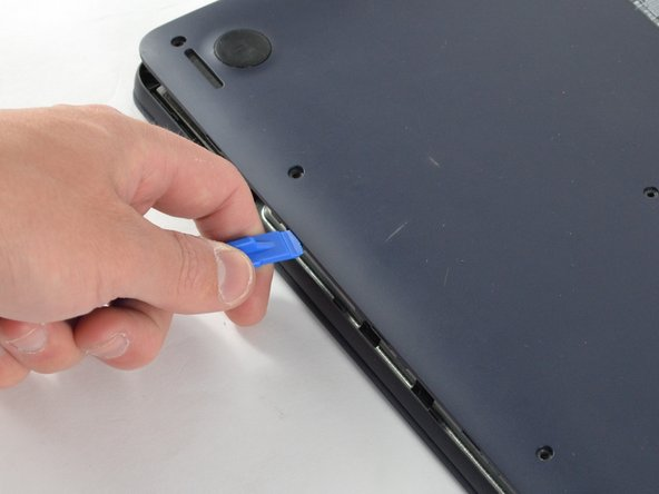 Insert the plastic opening tool in the crevice between the back of the laptop and the rest of the case (where the hinge is).