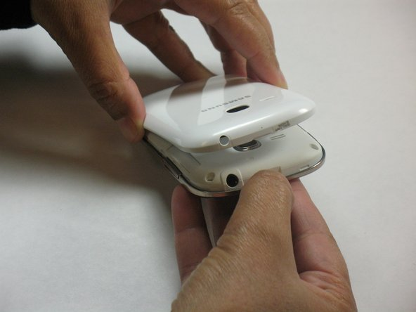 Turn the phone off and completely. Use your thumb nail or a plastic spudger to pry open the back cover,