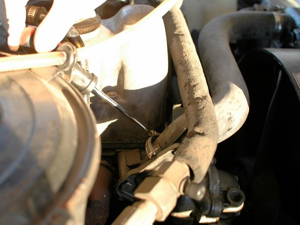 Use a Phillips head screw driver to loosen the hose clamp on the upper coolant hose where it attaches to the top of the thermostat housing.