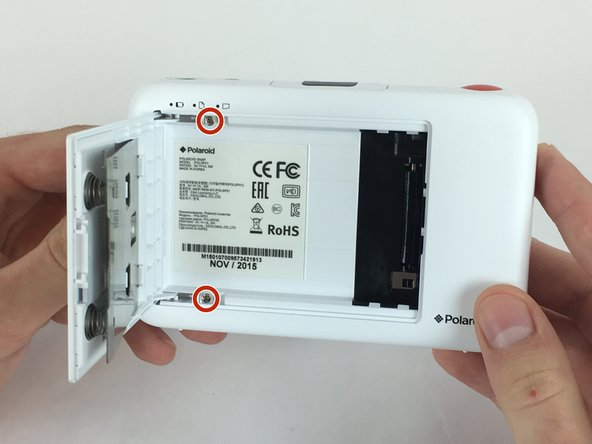 Open the paper door of the camera, then locate and remove the screws that are on the top and bottom edge of the inside of the camera.