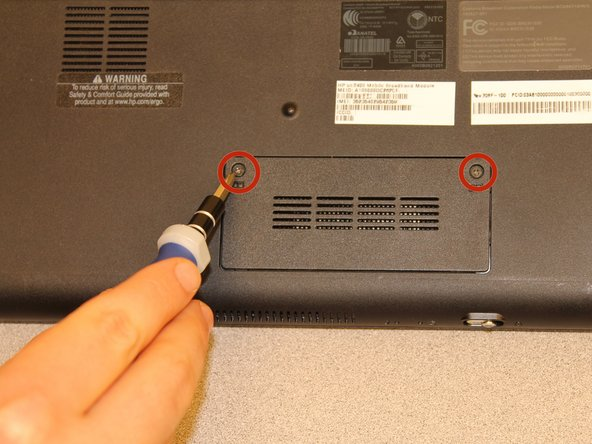 Flip the netbook over so you are looking at the bottom, and locate the two screws that hold the memory card cover.