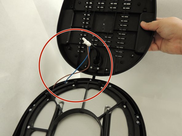 After removing the screws, carefully open the bottom cover.