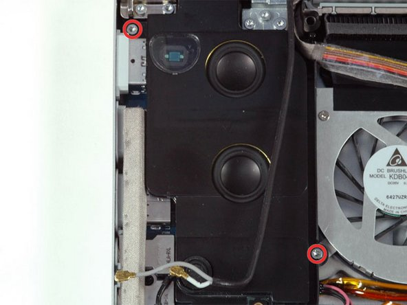 Remove the two 7.8 mm silver T6 Torx screws from the top left and bottom right corners of the left speaker assembly.