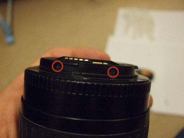 First, remove the two screws in the barrel of the lens with a philips 0 screwdriver