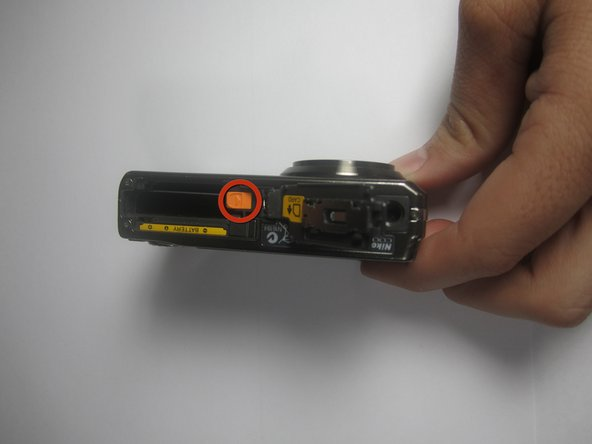 Slide the orange release button towards the center of the camera