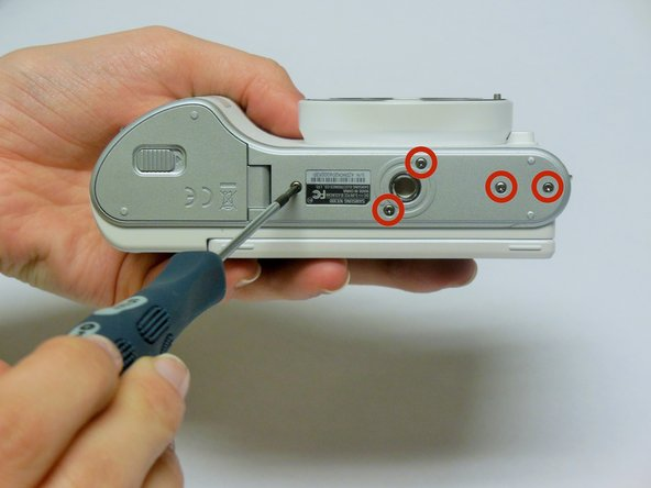 Using a Phillips #00 precision screwdriver, remove the seven 4mm screws (5 on the bottom of the device and 1 on each of the two sides) holding the back panel to the camera.
