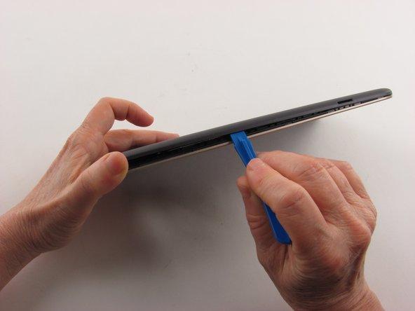 Insérez un outil d'ouverture en plastique dans la couture entre le boîtier arrière et l'écran.