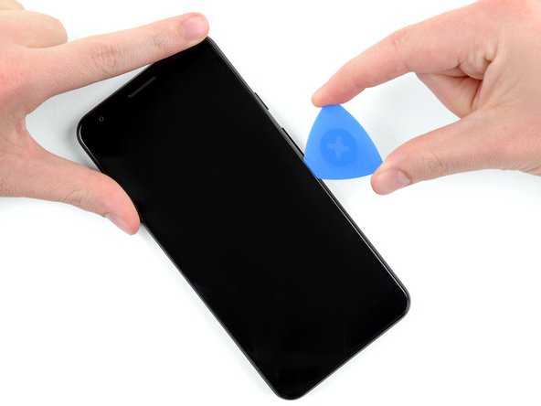 Once the pick is inserted, slide it up and down along the right edge of the phone to cut though the adhesive holding the screen in place.