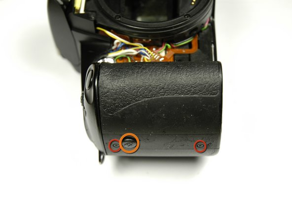 Using a 00 Phillips screw driver, unscrew the two 4.3 mm Phillips screws on the side of the camera.