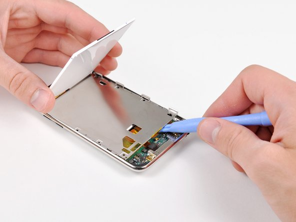 Lift the display out of the metal tray and rotate it toward the top edge of the Touch.