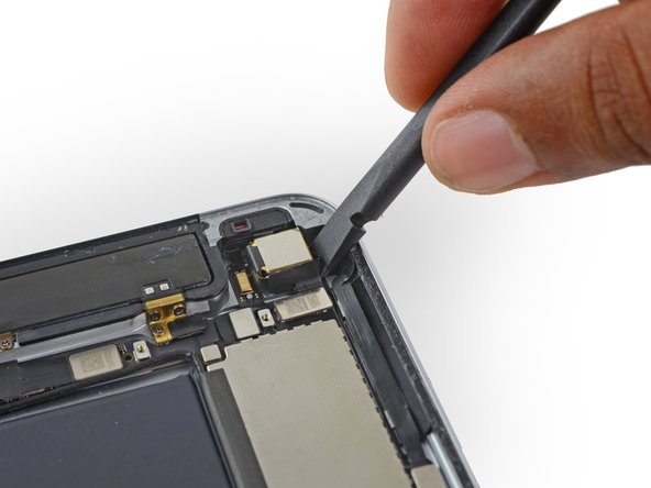 Use a spudger or plastic opening tool to pry the rear facing camera the rear enclosure.