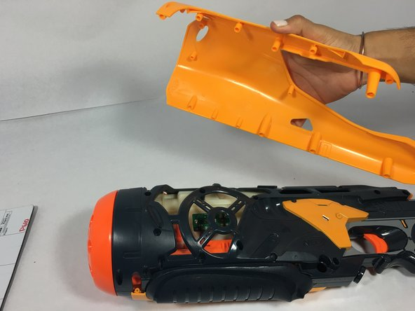 Remove the yellow and blue plastic covers from the Nerf gun to display the Nerf gun's motherboards and motor.