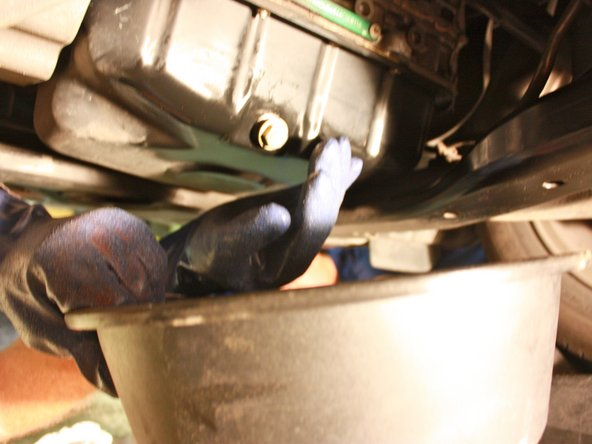 Loosen drain plug slowly by hand until the bolt is completely removed and oil begins to flow, re-positioning the oil drip pan if needed.