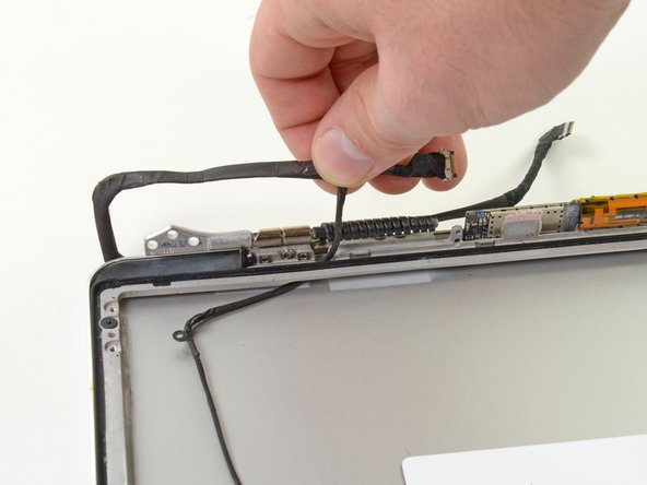 Carefully pull half of the AirPort/iSight cable through the opening located underneath the right hinge.