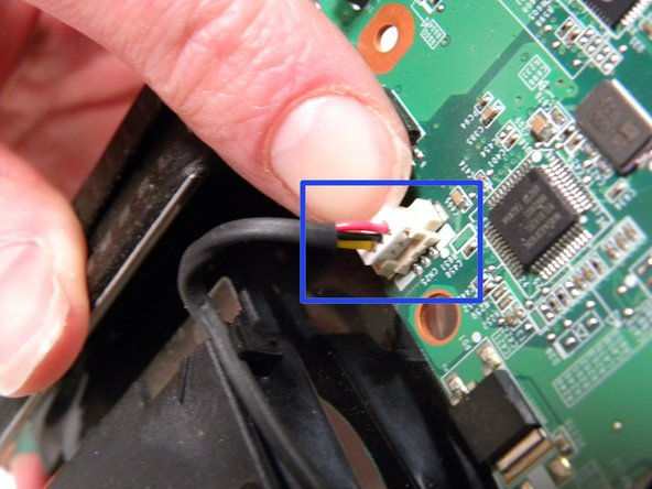 Disconnect the connector from the system board by pulling the white tab with your thumb and forefinger.