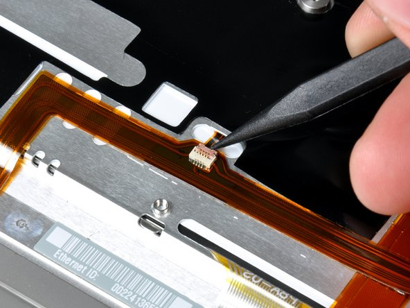 Use the tip of a spudger to flip up the brown plastic flap locking down the keyboard backlight ribbon cable.