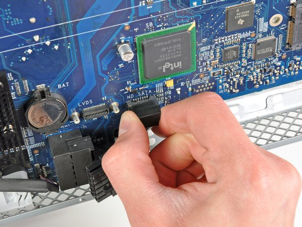 Pull the hard drive SATA data cable perpendicular to the face of the logic board to disconnect it from its socket.
