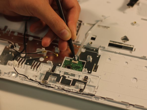 Using the pointed end of a spudger, lift up on the black latch that is holding the ribbon cable in place.