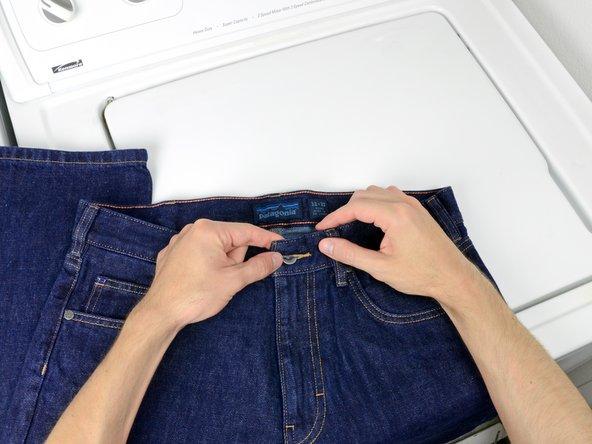 Knöpfen Sie die Jeans zu.