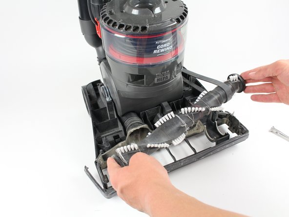 Grab on both ends of the roller brush, lifting it and the attached belt clear of the housing.