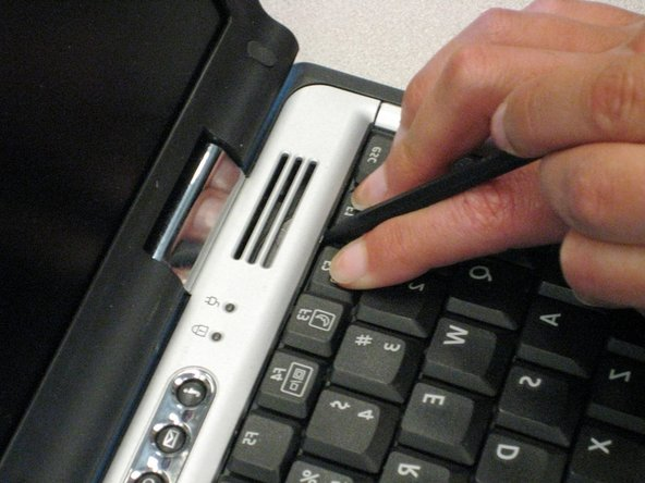While holding the Pause and Scroll keys, insert a spudger between the keys into the notch in the LED cover. Lift up.