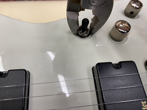 Remove the retaining nut that holds the pickup selector switch to the guitar.