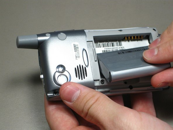 Lift the edge of the battery, separating contact points, and pull out as pictured.