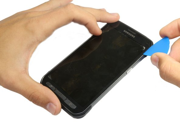 Use the pick to pry the sides and lower part of the display by sliding the pick through the phone.