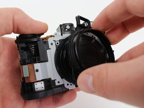 Remove the black plastic cover surrounding the lens by gripping and lifting upwards.