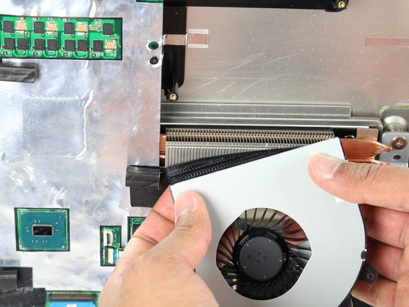 Remove the fan by peeling off the black electrical tape holding it against the heat sink vents.