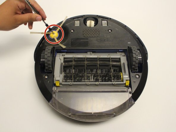 Flip the Roomba upside down. Using the Phillips #0 screwdriver, carefully remove the 5 mm screw holding the brush in place.