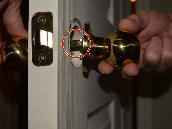 Align the door knob that goes on the outside of the room, aligning the peg and screw holes with the threaded cylinders of the latch mechanism.