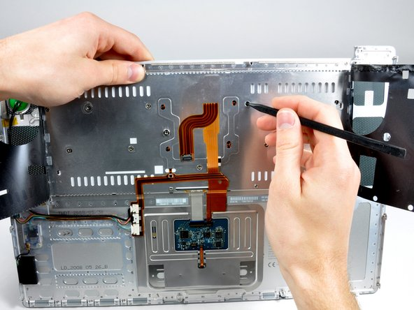 Place the upper casing on its edge and use a spudger to push the keyboard away from the casing, poking the spudger through the central keyboard screw hole. Grasp the keyboard as it separates from the casing.